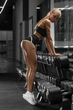 Ragazza atletica sexy che risolve nella palestra Donna di forma fisica che fa esercitazione Bei sexy si intromettono la cinghia immagine stock