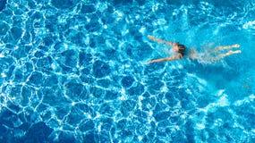 Ragazza attiva nella vista aerea del fuco della piscina da sopra, nuotate in acqua blu, vacanza tropicale, festa della giovane do immagine stock libera da diritti