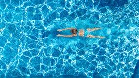 Ragazza attiva nella vista aerea del fuco della piscina da sopra, nuotate in acqua blu, vacanza tropicale, festa della giovane do immagini stock libere da diritti