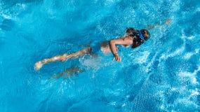 Ragazza attiva nella vista aerea del fuco della piscina da sopra, nuotate in acqua blu, vacanza tropicale, festa della giovane do fotografia stock libera da diritti