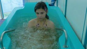 Ragazza attraente che bagna in un bagno in una stazione termale di salute Le ragazze godono dei bagni terapeutici all'aperto Immagine Stock Libera da Diritti