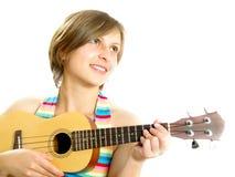 Ragazza attraente che gioca una chitarra hawaiana Fotografia Stock