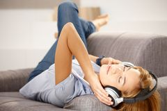 Ragazza attraente che gode della musica che pone sul sofà Immagini Stock