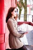 Ragazza attraente che legge un giornale sopra un muro di mattoni Immagine Stock Libera da Diritti