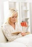 Ragazza attraente che legge un libro e che ha una tazza di caffè Fotografia Stock Libera da Diritti