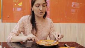 Ragazza attraente che mangia un pancake con il gelato in caffè, fine su stock footage