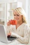 Ragazza attraente che per mezzo del computer portatile ed avendo una tazza di caffè Immagine Stock
