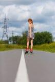 Ragazza attraente che rollerblading sulla strada fotografia stock
