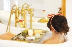 Ragazza attraente che si rilassa nel bagno su fondo leggero Fotografia Stock Libera da Diritti