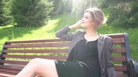 Ragazza attraente che si siede su un banco di parco sotto il sole Movimento lento Colpo di Stedicam video d archivio