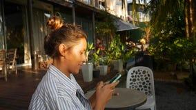 Ragazza attraente che si siede in un caffè e che scrive messaggio sul telefono video d archivio