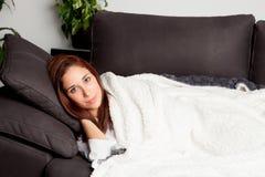 Ragazza attraente che si trova sullo strato coperto di coperta Fotografia Stock Libera da Diritti