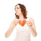 Ragazza attraente che tiene il cuore rosso di carta rotto del biglietto di S. Valentino Fotografia Stock