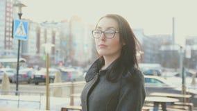 Ragazza attraente con i vetri ed il cappotto nei precedenti del paesaggio urbano Fotografie Stock