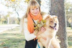 Ragazza attraente con il suo cane che indossa i vestiti caldi Immagini Stock Libere da Diritti