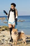 Ragazza attraente con il suo cane che indossa i vestiti caldi Immagine Stock
