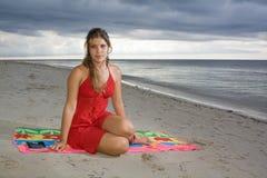Ragazza attraente con il vestito rosso, al lato di un libro Fotografia Stock
