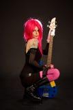 Ragazza attraente con la chitarra bassa fotografia stock libera da diritti