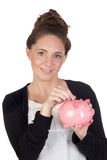 Ragazza attraente con la moneta dell'inserto del contenitore di soldi Immagini Stock