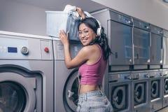 Ragazza attraente con un canestro nella lavanderia fotografie stock libere da diritti