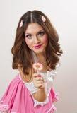 Ragazza attraente con una lecca-lecca in suo vestito da rosa e dalla mano isolato su bianco. Gioco castana dei bei capelli lunghi  Fotografia Stock