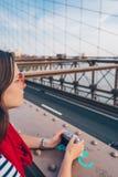Ragazza attraente con una macchina fotografica sul ponte di Brooklyn immagine stock libera da diritti