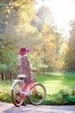 Ragazza attraente dai capelli lunghi alla moda bionda in breve vestito con la bicicletta di signora in parco soleggiato fotografia stock