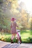 Ragazza attraente dai capelli lunghi alla moda bionda in breve vestito con la bicicletta di signora in parco soleggiato immagine stock