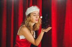 Ragazza attraente della neve in un vestito ed in un cappello rossi su un fondo di curtainsr rosso immagini stock libere da diritti