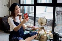 Ragazza attraente ed alla moda asiatica che mangia il gelato e che prende un colpo della foto del selfie fotografie stock