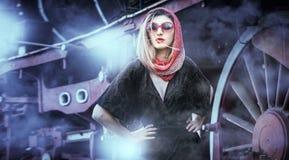 Ragazza attraente sexy con i vetri della sciarpa e di sole della testa di rosso che posano sul binario davanti ad un treno d'anna Fotografie Stock