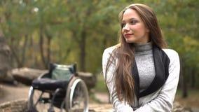 Ragazza attraente su una sedia a rotelle che si siede sulla pietra nel parco di autunno Svago disabile archivi video