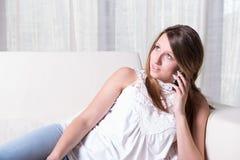 Ragazza attraente sul telefono con gli amici Immagine Stock
