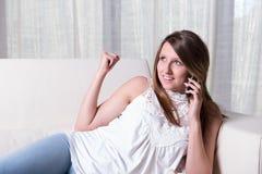 Ragazza attraente sul telefono con incoraggiare degli amici Immagine Stock Libera da Diritti