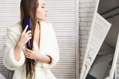 Ragazza attraente in un accappatoio bianco che pettina capelli che stanno davanti allo specchio all'interno del bagno fotografia stock libera da diritti