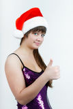 Ragazza attraente in un cappello di natale con il pollice in su Fotografia Stock Libera da Diritti