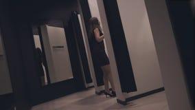 Ragazza attraente in un deposito di modo che prova su un vestito video d archivio