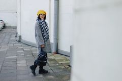 Ragazza attraente in vetri in cappotto e nella camminata gialla di stile libero del berretto fotografia stock libera da diritti
