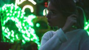 Ragazza attraente in vetri che posano nel parco di amusment vicino all'attrazione archivi video