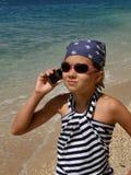 Ragazza (bambino) con la cella sulla spiaggia della sabbia Fotografia Stock