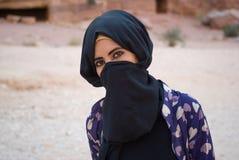Ragazza beduina, con il fronte nascosto dietro il velo, PETRA, Giordania Fotografie Stock