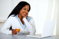 Ragazza bella dell'allievo che sorride e che osserva al computer portatile Fotografia Stock Libera da Diritti
