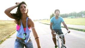 Ragazza bella giovane che posa ed alta--fiving il suo amico mentre ciclare, classificato stock footage