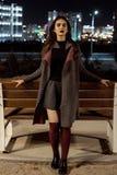 Ragazza bella giovane in un cappotto grigio con le pose nella sera fotografie stock libere da diritti