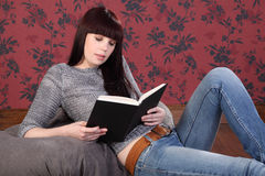 Ragazza bella nel paese sul sacchetto di fagiolo che legge un libro Fotografia Stock Libera da Diritti
