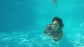 Ragazza bianca nel ballare del bikini subacqueo davanti all'obiettivo in stagno blu Vista da underwater archivi video