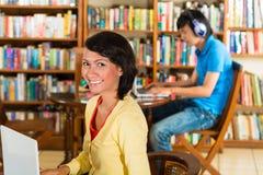Ragazza in biblioteca con il computer portatile Immagini Stock