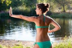 Ragazza in bikini che pratica 'chi' del tai accanto ad un fiume Immagine Stock