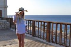 Ragazza in bikini che si rilassa in costume da bagno e con il vestito leggero dalla spiaggia sul terrazzo con il mare blu ed il c fotografia stock libera da diritti