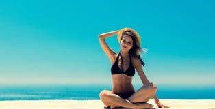 Ragazza in bikini con il mare blu e cielo su fondo fotografie stock libere da diritti